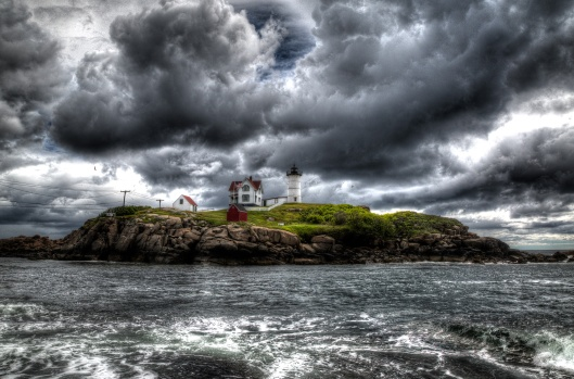 Standing against the approaching weather, Nubble Light provides a beacon of hope and safety.